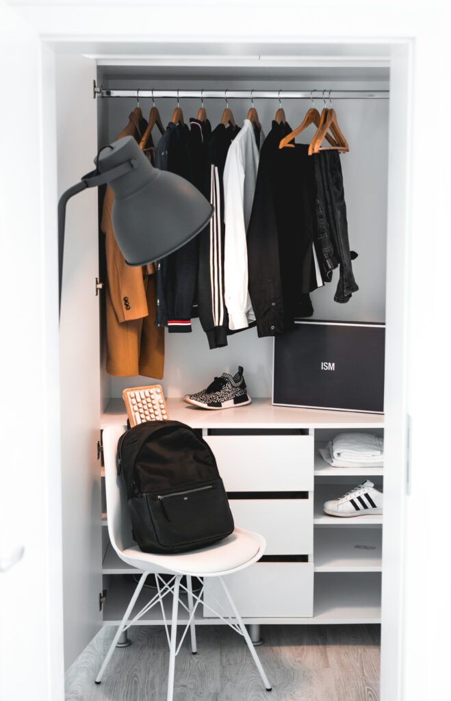 White Organized Closet With Shirts And Backpack